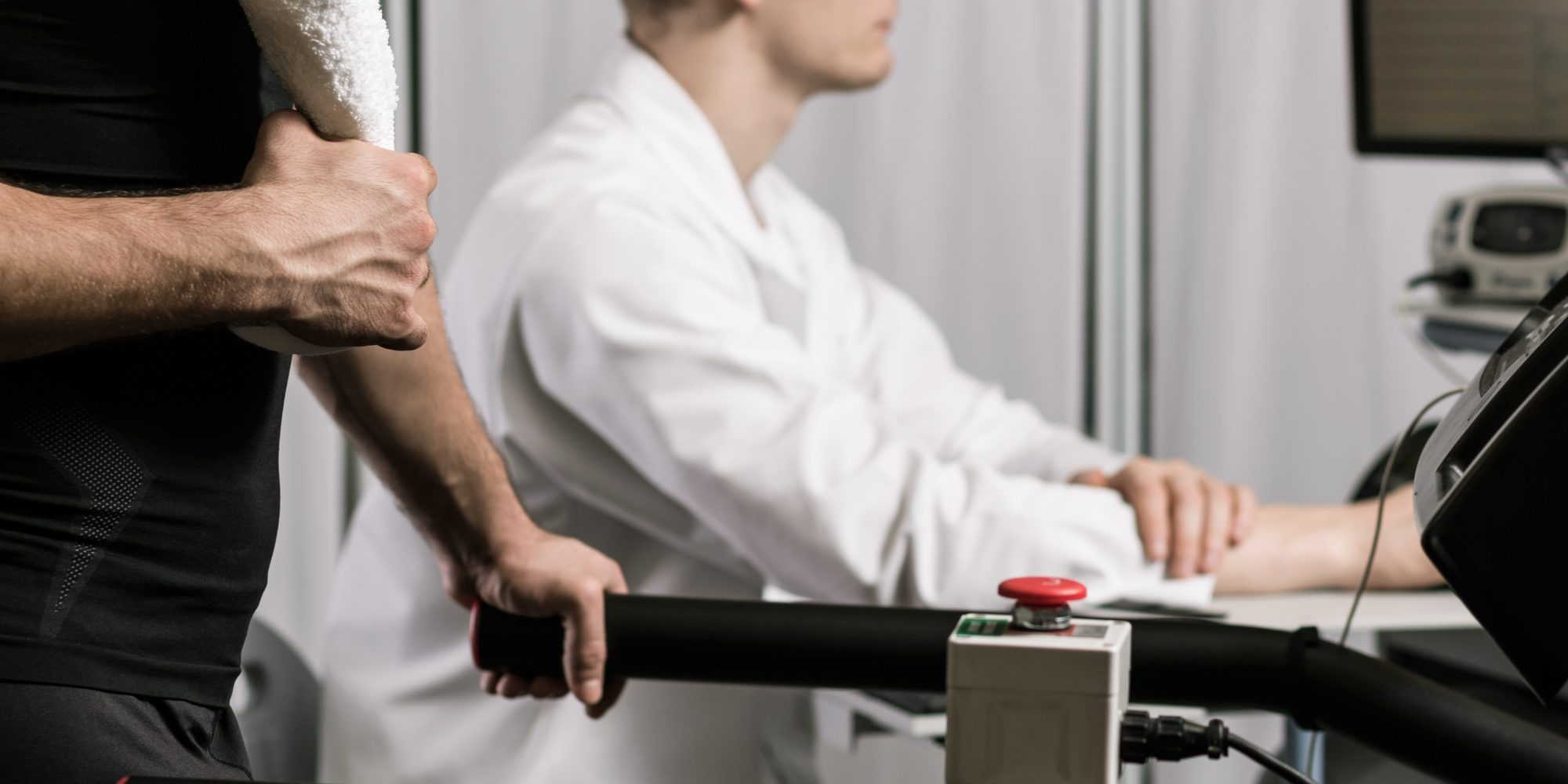 Young muscular athlete walking on treadmill during examination. Doctor checking his patient's aerobic capacity