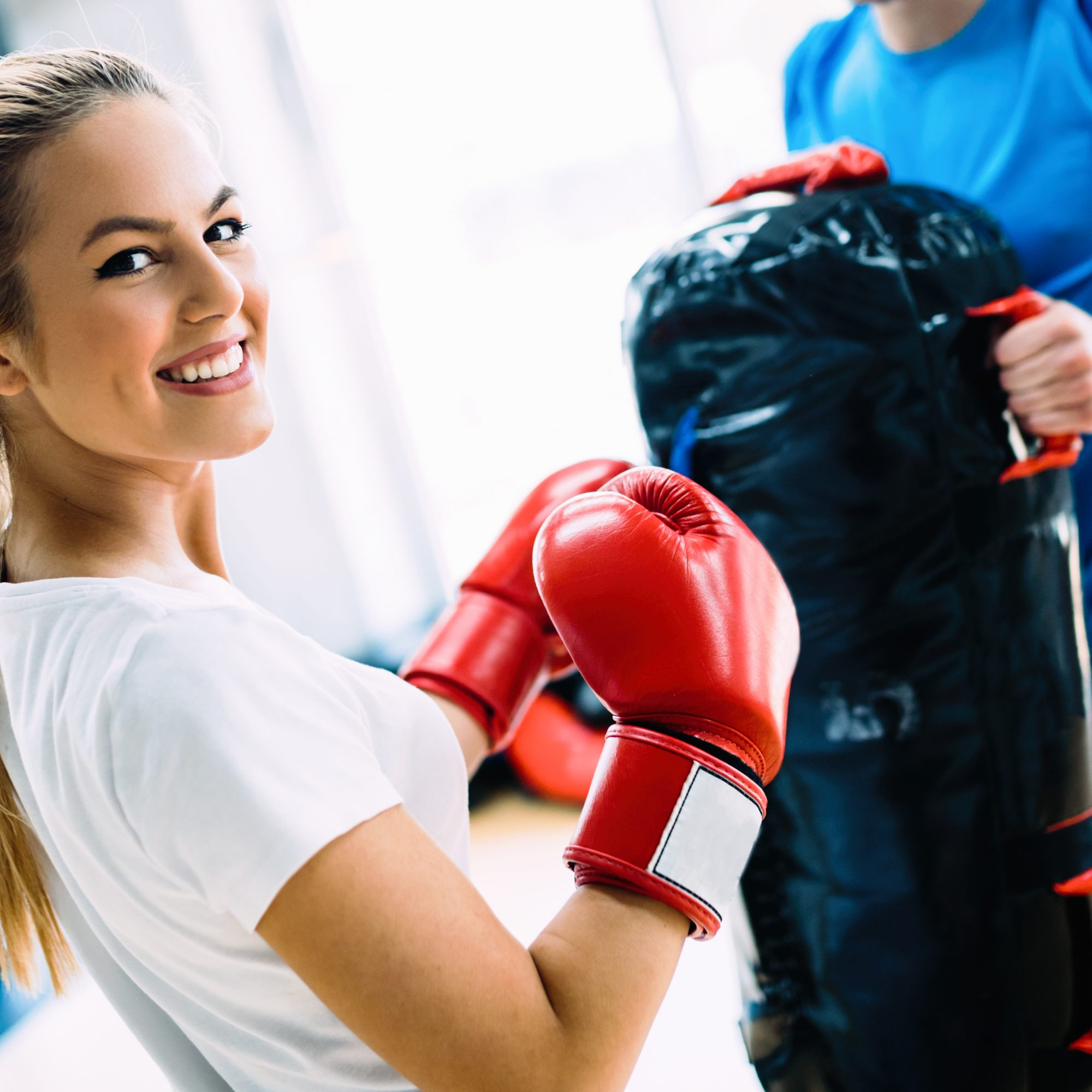 Portrait of beautiful woman wearing boxing gloves in gym